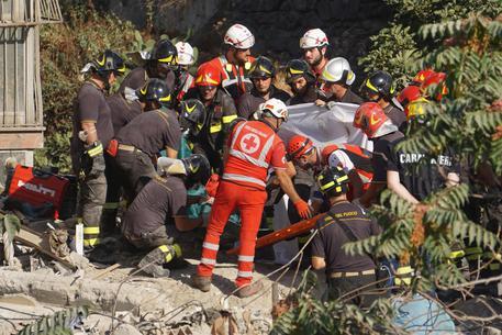 I vigili del fuoco estraggono l'ultimo corpo dalle macerie della palazzina crollata a Torre Annunziata, Napoli, 8 luglio 2017.ANSA/CESARE ABBATE/